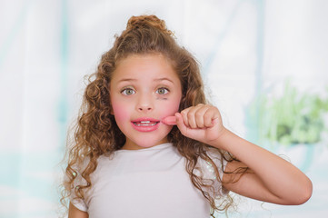 Close up of little surprised beautiful girl using wrong a lipstick in a blurred background