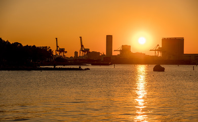 Sunset over Tokyo bay viewed from Odaiba with buildings silhouted against orange sky