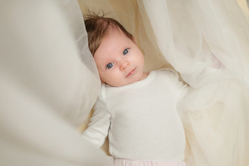 Adorable two months old baby wrapped in white fabric