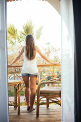 Young beautiful girl sitting on a chair on the balcony of the hotel and looks on palms and sea