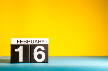 February 16th. Day 16 of february month, calendar on yellow background. Winter time. Empty space for text