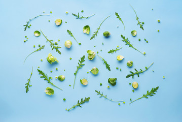 Top view of a pattern of vegetables on a pastel blue background.