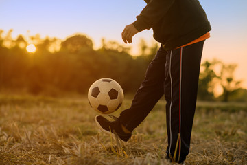 Asian boy kicking soccer in the sunset background