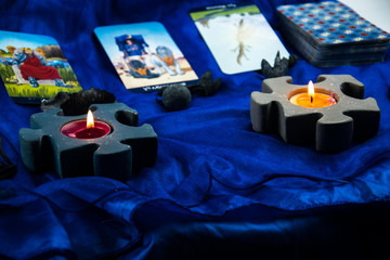 candlesticks in the form of two puzzles with tarot cards in the background on a blue background