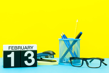 February 13th. Day 13 of february month, calendar on yellow background with office supplies. Winter time