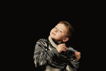 Beautiful boy with camera in Studio on dark background
