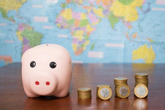 piggy bank with coins and   on a wood table with a map on the back (cofrinho com moedas sobre uma mesa de madeira e com um mapa de fundo)