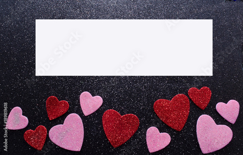 A shiny black background with Valentine's day hearts at the bottom