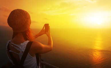 woman take picture on mobile phone at sunset