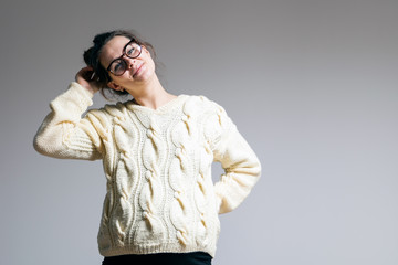 Young woman in a woolen sweater of milky color on the last days of pregnancy posing on a white isolated background