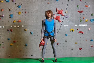Active young man in sportswear standing on green mat against climbing wall
