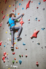 Below view of young active man with rope around his waist and legs climbing wall in gym