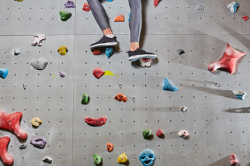 Lower part of climber legs in leggins and sports-shoes standing on grips of wall
