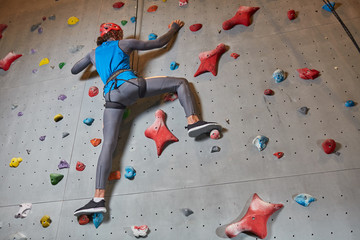 Below view of active climber in protective helmet and sportswear training on climbing wall