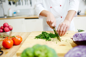 Chef cutting greenery on wooden board in the kitchen while cooking vegetarian food