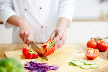 Chef of restaurant cutting red pepper in two halves while cooking meal from vegs