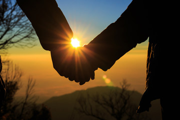 Couple holding by hands on beautiful sunset