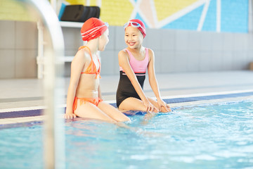 Cute smiling Asian girl listening to her friend while sitting by water of swimming-pool