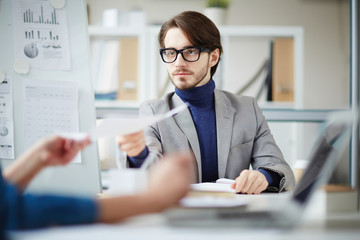 Young professional passing over paper to colleague or business partner to read