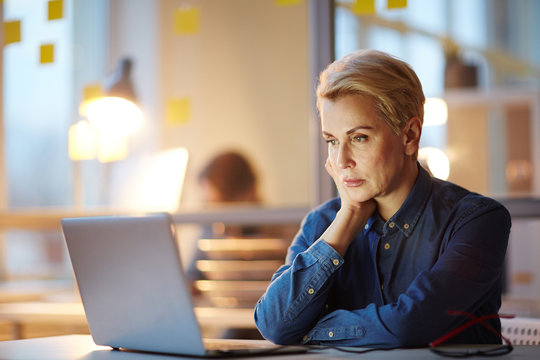 Mature professional watching online conference or webinar in laptop while sitting in office