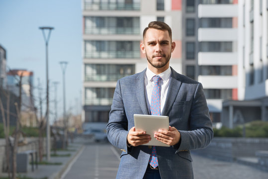 Businessman or real estate agent with tablet computer against new building