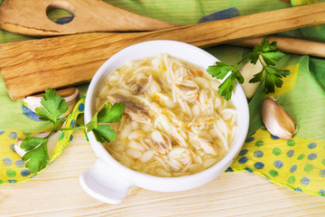 noodle soup with chicken and parsley on tablecloth and wooden table