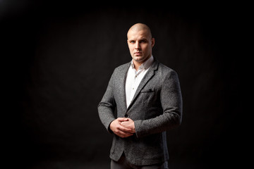 Young bald man in gray suit and white shirt posing on black isolated background