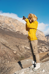 A girl photographer in a fur hat and a yellow sweater in the mountains takes pictures on her digital camera.
