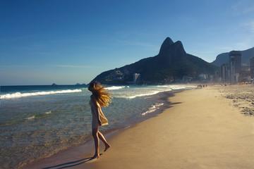 young woman walking at Copacabana beach in Rio de Janeiro