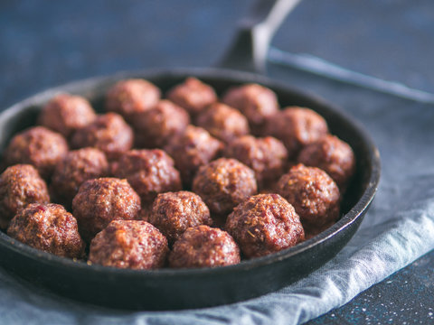 Homemade roasted beef meatballs in cast-iron skillet on dark blue background. Copy space for text. Shallow DOF