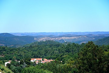 Elevated view of the mountains and countryside in the Monchique mountains with a small village in the foreground, Algarve, Portugal.