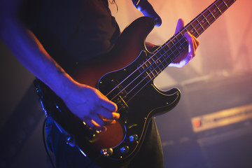 Electric bass guitar player, close up photo