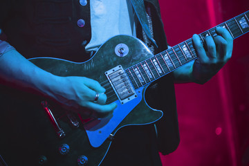 Guitarist plays electric guitar on stage