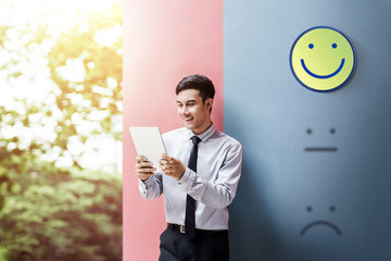 Customer Experience Concept, Happy Businessman Enjoying on digital Tablet with Smiley Face Rating for a Satisfaction Survey