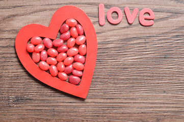 Red jelly beans displayed in a red heart shape with the word love