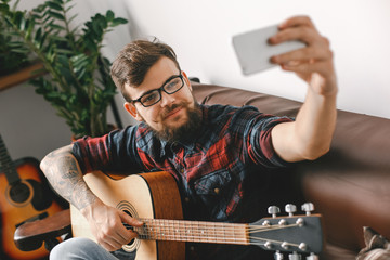 Young guitarist hipster at home holding guitar taking photos smiling