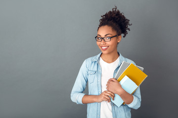 Young african woman isolated on grey wall studio casual daily lifestyle student holding notebooks smiling