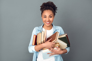 Young african woman isolated on grey wall studio casual daily lifestyle standing with books joyful