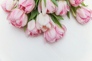 Bouquet of pink tulips over shabby white wooden table. Spring greeting card happy mother day copy space