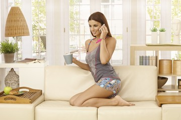 Young woman talking on mobile at home