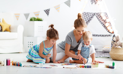 children's creativity. mother and children draw paints in   playroom