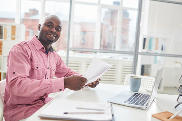 Happy young African-american businessman with papers sitting by desk and analyzing information during working day