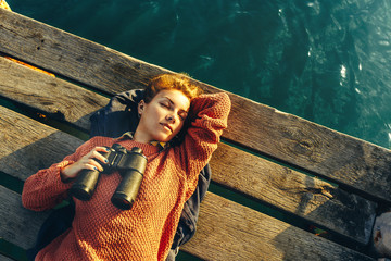 Beautiful Young Girl Lies On Pier, Holds Binoculars In Hand And Dreams, Top View