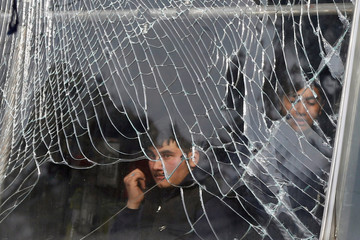 Shopkeeper looks on behind broken glass of his shop, near the site of a car bomb attack in Kabul