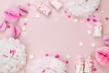 Frame made of Decorative Baby milk bottles with candy and paper decorations for Baby shower party. Flat lay, top view