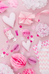Frame made of Pink and white Paper Decorations, candy, hearts, gifts, confetti for Baby party. Flat lay, top view