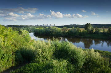 summer landscape. High grass and river under the blue sky