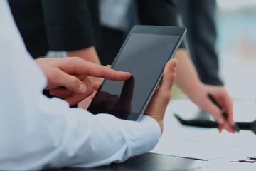 Businessman holding digital tablet at meeting.