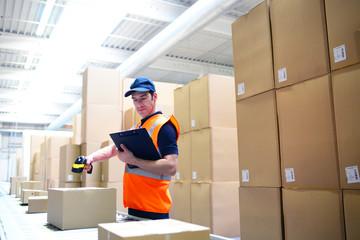 Arbeiter im Versandhandel scannt Pakete am Fliessband zur Lieferung ein // Mail-order workers scan packages on conveyor belt for delivery
