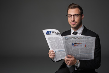 Portrait of smiling bearded businessman keeping modern newspaper. He looking at camera. Information concept. Isolated and copy space